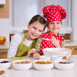 Lyckliga systrar som tillsammans lagar mat Fotografering för Bildbyråer