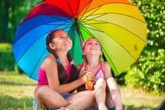 Lyckliga systrar under det färgrika paraplyet parkerar in Royaltyfri Foto