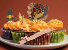 Lyckliga tacksägelsemuffin med kalkon, festmåltid, och vallfärdar hatttoppergarneringar - closeup. royaltyfri foto