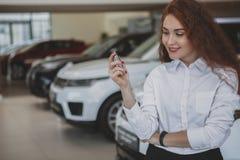 Lyckliga tangenter för kvinnainnehavbil till hennes nya bil royaltyfria bilder