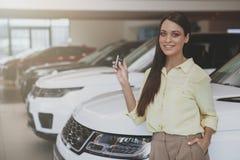 Lyckliga tangenter för kvinnainnehavbil till hennes nya bil royaltyfri fotografi