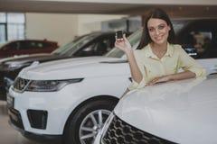 Lyckliga tangenter för kvinnainnehavbil till hennes nya bil arkivbilder