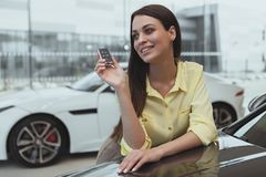 Lyckliga tangenter för kvinnainnehavbil till hennes nya bil arkivfoton