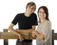 Lyckliga Teen par vid staket Arkivfoton