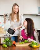 Lyckliga tillfälliga kvinnor som lagar mat mat Royaltyfri Foto