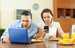 Lyckliga tillfälliga par genom att använda elektroniska apparater Royaltyfri Fotografi