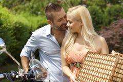 Lyckliga tillfälliga par med sparkcykel- och picknickkorgen Arkivfoto