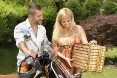 Lyckliga tillfälliga par med sparkcykel- och picknickkorgen Arkivbilder