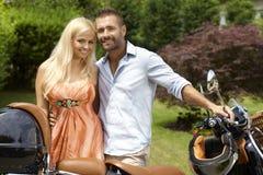 Lyckliga tillfälliga par med sparkcykeln i utomhus- trädgård Arkivfoto