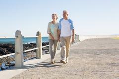 Lyckliga tillfälliga par som går vid kusten Arkivfoton