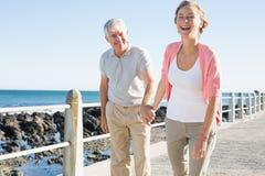 Lyckliga tillfälliga par som går vid kusten Arkivfoto