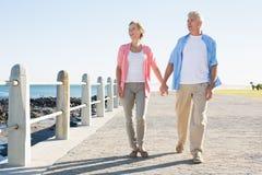 Lyckliga tillfälliga par som går vid kusten Fotografering för Bildbyråer