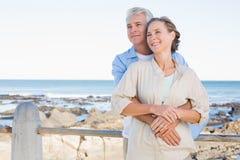 Lyckliga tillfälliga par som kramar vid kusten Arkivfoto