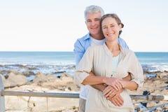 Lyckliga tillfälliga par som kramar vid kusten Arkivbild