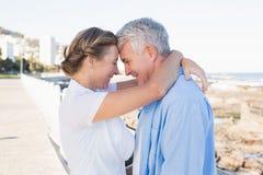 Lyckliga tillfälliga par som kramar vid kusten Arkivbilder