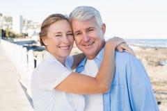 Lyckliga tillfälliga par som kramar vid kusten Royaltyfri Bild