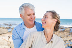 Lyckliga tillfälliga par som kramar vid kusten Royaltyfri Fotografi