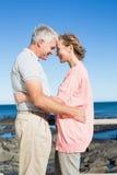 Lyckliga tillfälliga par som ler på de vid kusten Arkivbilder