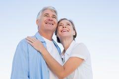 Lyckliga tillfälliga par som omfamnar under blå himmel Royaltyfria Foton