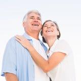 Lyckliga tillfälliga par som omfamnar under blå himmel Arkivbild