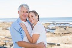Lyckliga tillfälliga par som omfamnar vid havet Arkivfoton