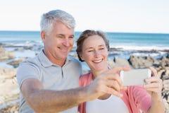 Lyckliga tillfälliga par som tar en selfie vid kusten Royaltyfri Foto