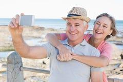 Lyckliga tillfälliga par som tar en selfie vid kusten Royaltyfria Bilder