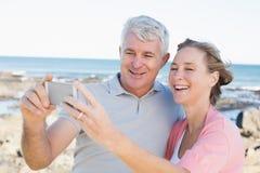 Lyckliga tillfälliga par som tar en selfie vid kusten Royaltyfri Bild