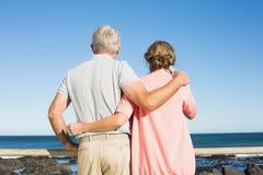 Lyckliga tillfälliga par som ut ser till havet Arkivbilder