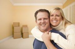 Lyckliga tillgivna par i rum av det nya huset med askar Royaltyfri Foto