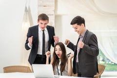 Lyckliga timmar! Sammanträde för tre affärsman på tabellen och sitter och Arkivbild
