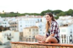 Lyckliga tonåriga beskåda sikter som sitter på en avsats royaltyfri bild