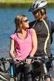Lyckliga tonåriga cyklister som omfamnar på lakesiden Royaltyfri Foto