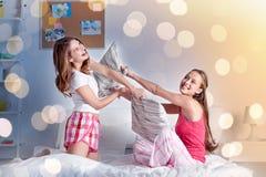 Lyckliga tonåriga flickavänner som hemma slåss kuddar royaltyfri foto