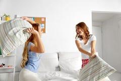 Lyckliga tonåriga flickavänner som hemma slåss kuddar arkivbilder