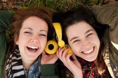 Lyckliga tonåriga flickor som delar musik Royaltyfria Bilder