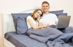Lyckliga tonåriga par genom att använda bärbara datorn på säng på sovrummet Ungt gift par som hemma ligger p? s?ng och anv?nder b royaltyfria bilder