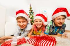 Lyckliga tonåriga ungar med jultomtenhattar och leenden Fotografering för Bildbyråer