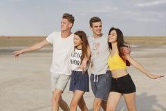 lyckliga tonåringar Grupp av tonårs- ungar på en suddig naturlig bakgrund Två unga par i en parkera stående två för pelikan för k royaltyfri foto