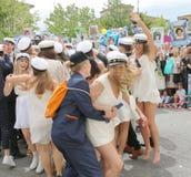 Lyckliga tonåringar som bär avläggande av examen, caps att fira graduatien Royaltyfria Foton