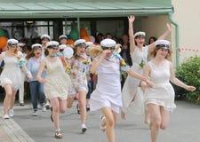 Lyckliga tonåringar som bär avläggande av examen, caps att fira graduatien Arkivfoton