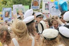 Lyckliga tonåringar som bär avläggande av examen, caps att fira graduatien Arkivbilder