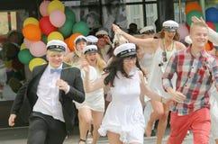 Lyckliga tonåringar som bär avläggande av examen, caps spring ut från skola Royaltyfria Foton