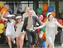Lyckliga tonåringar som bär avläggande av examen, caps spring ut från skola Royaltyfri Foto