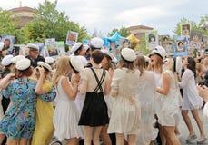 Lyckliga tonåringar som dansar på avläggandet av examen Royaltyfria Foton