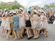 Lyckliga tonåringar som dansar på avläggandet av examen Arkivfoto