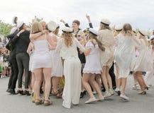 Lyckliga tonåringar som dansar på avläggandet av examen Arkivbild