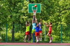 Lyckliga tonåringar som spelar basket på lekplats Royaltyfria Foton