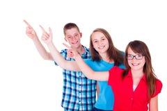 Lyckliga tonåringar som upp till pekar kopieringsutrymme Royaltyfria Foton