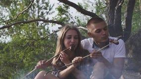 Lyckliga tonåringpar äter korvar som stekas på rökig brasa i skogen på vandringen arkivfilmer